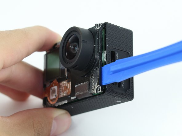 Image 2/2: Using the plastic opening tool, slowly pry open the motherboard assembly.