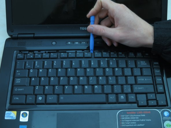 Use a plastic opening tool to pry the top of the keyboard loose from its casing.