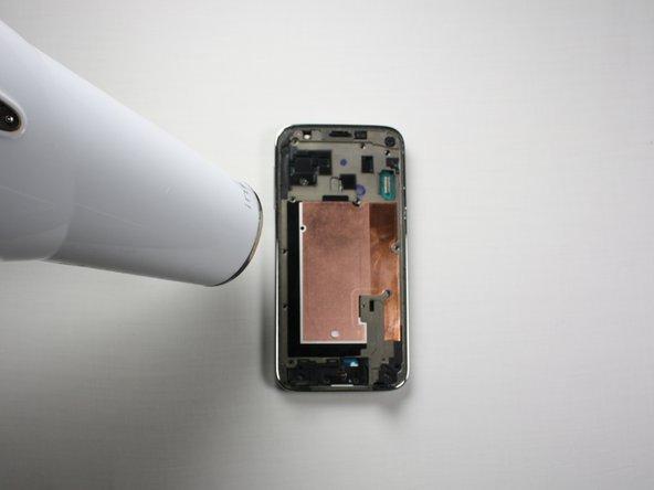 Riscalda il perimetro del telaio centrale con un asciugacapelli oppure usa un iOpener per ammorbidire l'adesivo sul telaio stesso.