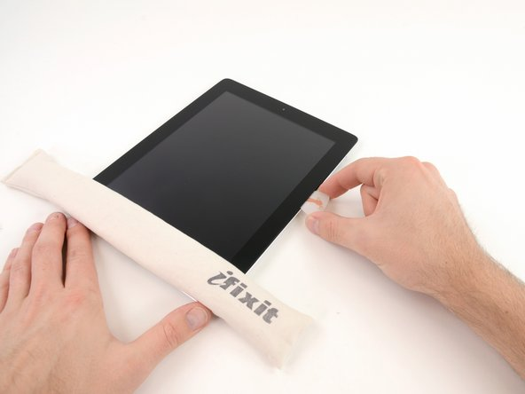 Image 1/3: It may be necessary to move the heated iOpener back onto the right edge of the iPad as you release the adhesive. This depends on how long the iPad has been able to cool while you were working on it.
