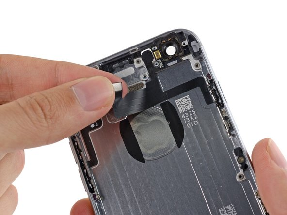 Image 2/3: Remove the flash/microphone/power button assembly cable from the phone.