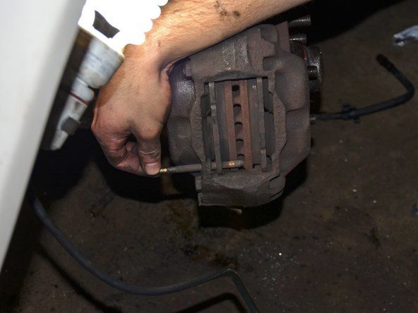 Remove the two brake pad dowels by sliding them towards the car through their holes in the brake caliper. You may have to use a punch or screwdriver to get them to start moving.