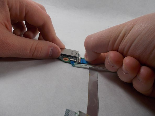 Pull on the blue tab of the ribbon cable to remove the ribbon cable.