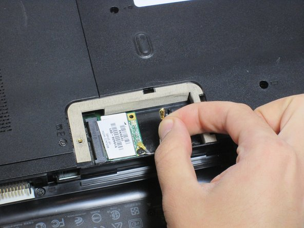 Image 2/3: Remove the 3mm screw holding the Wi-Fi module using a Phillips #0 screwdriver.