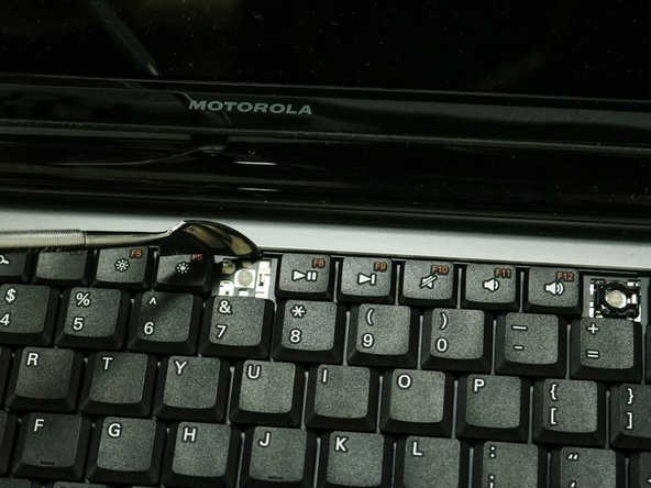 You can use the a small metal spudger to depress each tab to avoid scratching the keyboard.