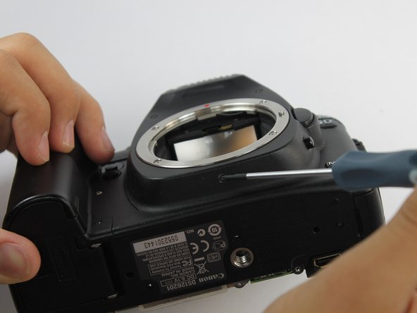 Remove the single screw underneath where the lens would be using a Phillips #0.