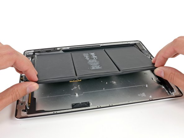 Image 1/2: Gently lift the left side of the battery up, rotating it toward the right side of the iPad.