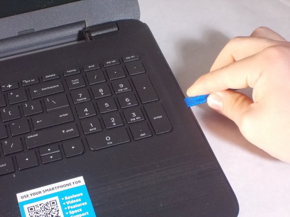 Carefully use the blue plastic opening tool to pry the clam shell of the laptop apart.