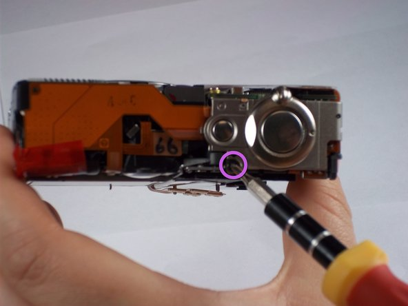 Remove one 4.3mm screw directly below the power button on the top of the camera.