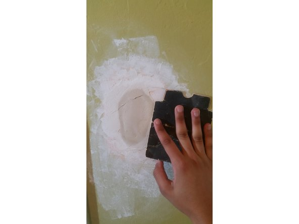 Image 1/1: Sand the spackle until it is smooth and flush with the wall.