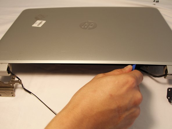 When sliding with plastic opening tool, be careful around the webcam location to prevent damage.