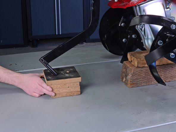 Place a block (or blocks) of wood under the tiller's drag bar to prevent the tiller from leaning back.