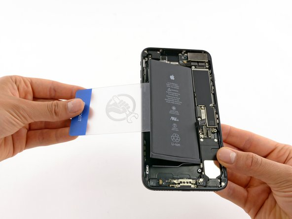Image 2/2: After about a minute, remove the iOpener, flip the phone over and slide a plastic card underneath the battery to break up any remaining adhesive behind the battery.