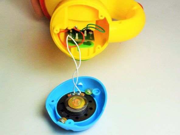 Once the screws have been removed, pull the housing away from the yellow body of the flashlight. Be careful not to disconnect the white wires from the speaker, unless speaker replacement is required.