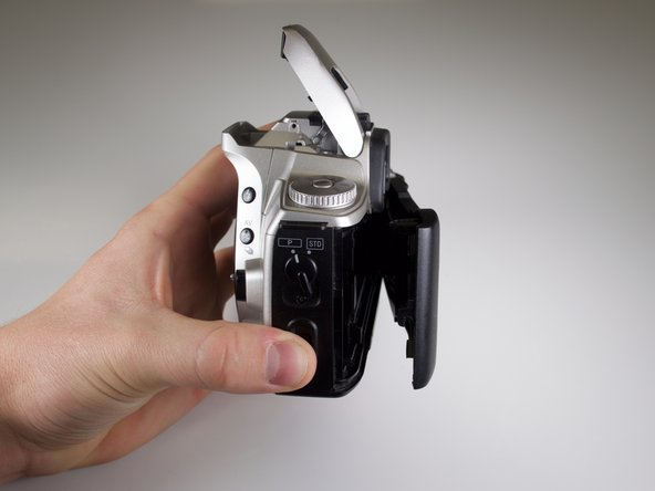 Open the back panel by firmly pressing up on the back-cover release on the lower right side of the camera.