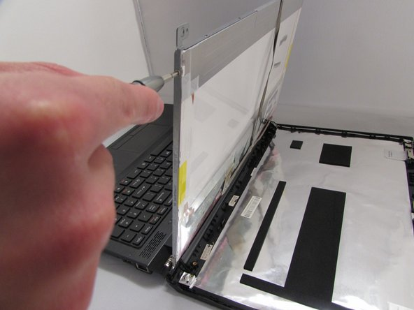 Using the Phillips #0 Screwdriver,  remove the four 2.9 mm screws  from each side of the bracket that holds the display panel in place.