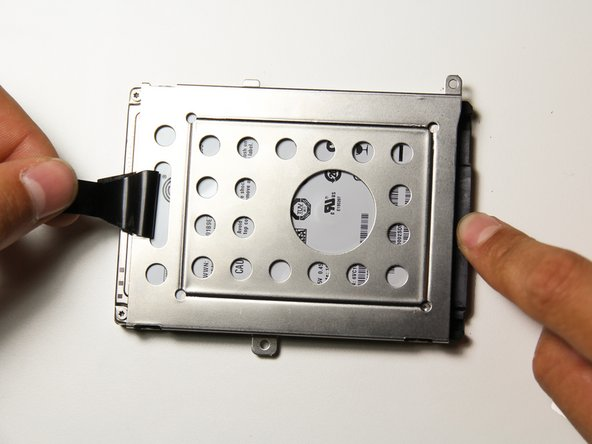 Using the tab on the hard drive case, pull the case up and away from the hard drive to remove it.