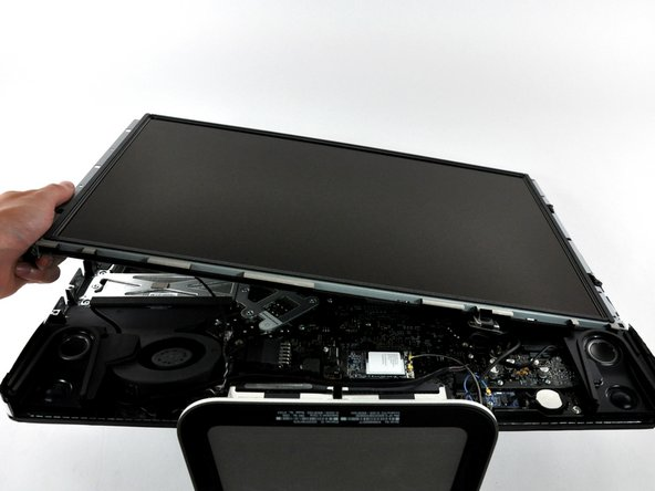Image 2/2: Lift the display panel from its left edge and rotate it toward the right edge of the iMac.