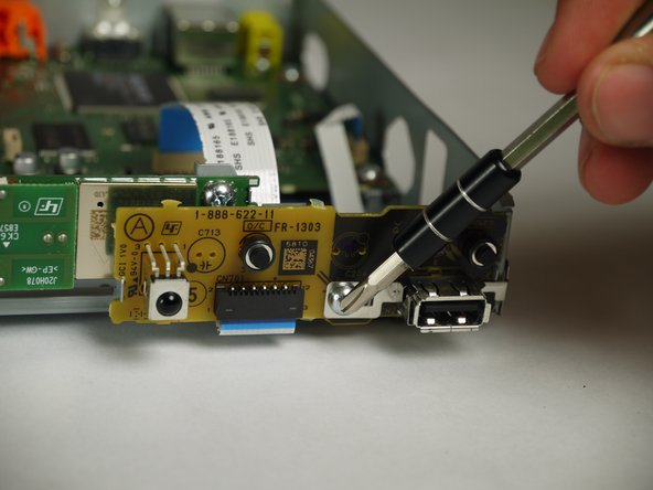 Using the Phillips #2 screwdriver, unscrew the silver, 8mm screw holding the board in place.