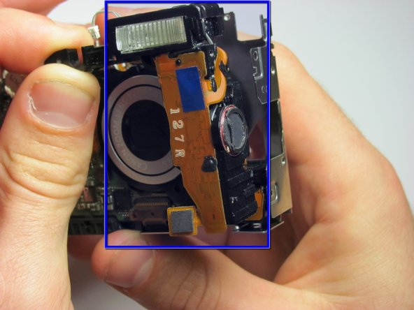 Then, maneuver the flash along with its components (capacitor and speaker) out of the camera.