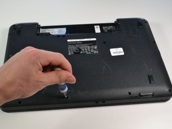 "Remove the two 5/16"" screws from the bottom of the laptop using a #0 philips head screwdriver."