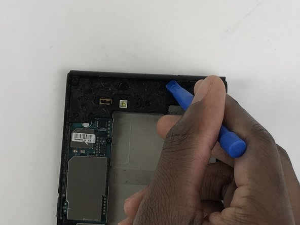 Use a plastic opening tool to remove the plastic piece in the upper part of the phone.