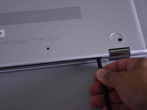 Use the nylon spudger to pop off the bottom cover by inserting it into the heat vent and twisting to the left or right.