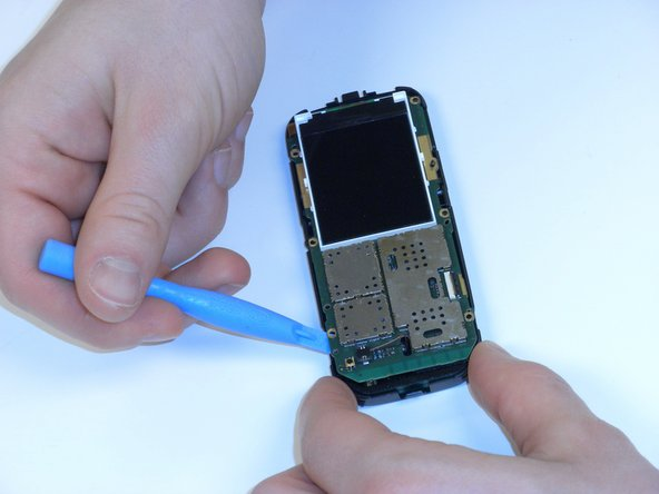 Using the plastic opening tool, gently pry off the motherboard from the plastic shell.