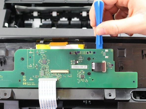 Insert the plastic opening tool into the space between the green board and the printer manifold and push downwards to dislodge the green board.
