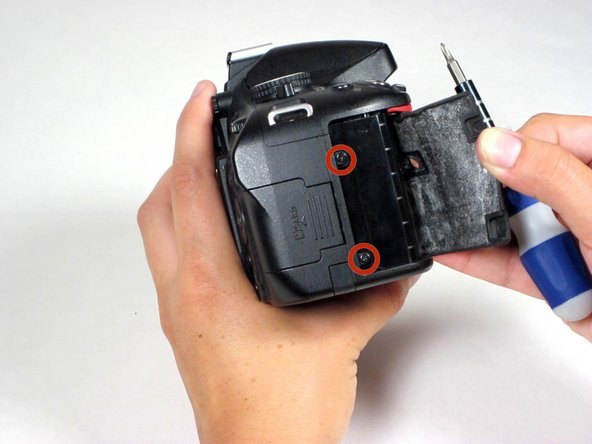 Carefully peel back the black rubber hand grip, which is attached to the chassis with a strong adhesive, and remove the two screws concealed underneath.
