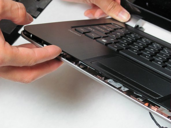 Use a spudger to lift the keyboard plate off of the base of the computer.