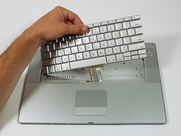 Slide the keyboard away from the trackpad and out of the upper case.