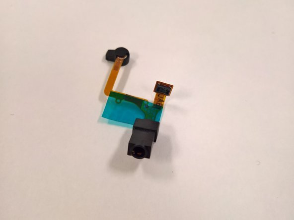 Image 3/3: After lifting the audio jack off the adhesive, remove it from the device.