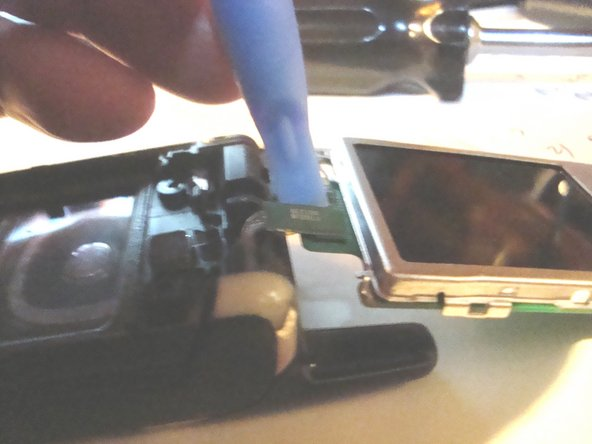 Use a plastic opening tool to gently pry the LCD ribbon cable connector up out its socket on the LCD circuit board.