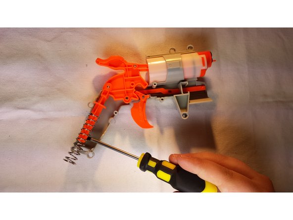 Image 1/1: Carefully slide out the big spring and fit in your replacement (thin-coil end coiled around the orange plastic)