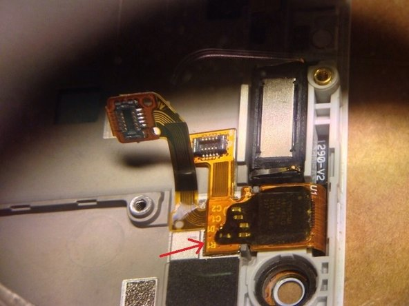 Image 1/1: The flex cable is held down with a bit of adhesive, just use your spudger to carefully peel it up.