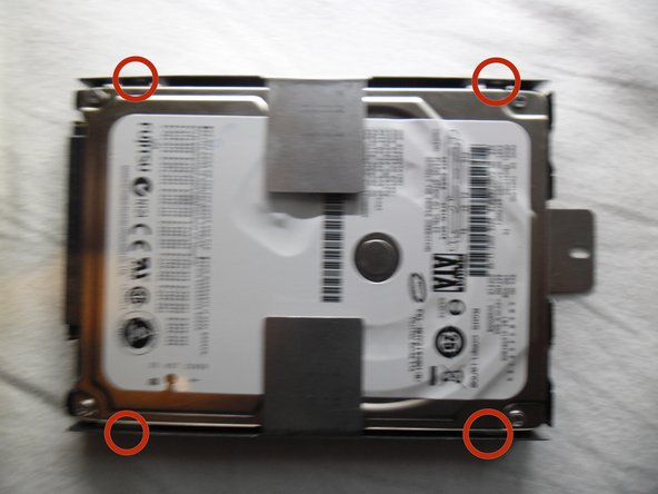 There is a screw on each corner of the hard drive bracket. To take the hard drive out of its bracket you need to remove the 4 screws.