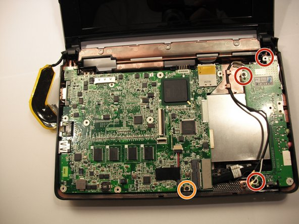 Image 1/1: Remove a single 3.9 mm Phillips #0 screw from the front of the motherboard.
