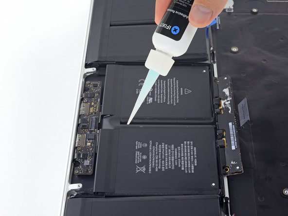With the left edge of your MacBook Pro still propped up, apply a few drops of adhesive remover  down the center line between the two middle battery cells.