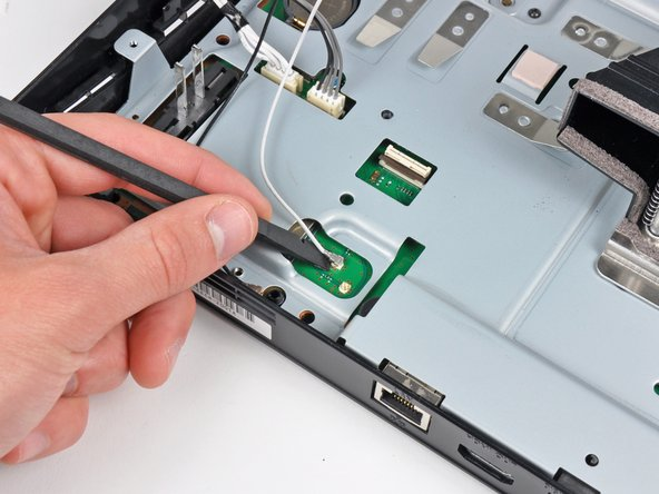 Image 2/2: Use the flat end of a spudger to pry both antenna connectors up from their sockets on the motherboard.