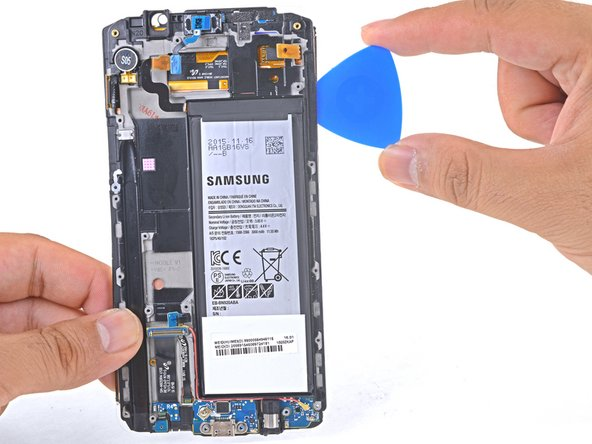 Slide the opening pick down the battery-side of the phone, separating the adhesive.