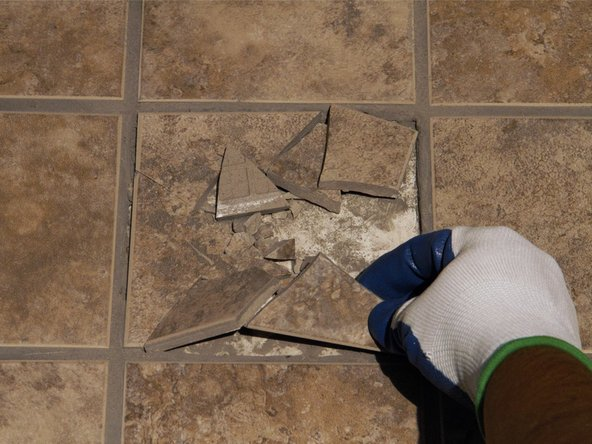 Remove the broken pieces of tile, using gloved hands for large pieces or a broom for smaller shards.