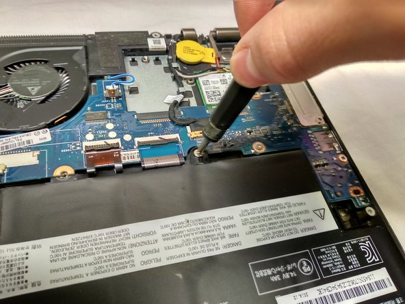 Remove the one and only Phillips screw with a Phillips 0 screwdriver.