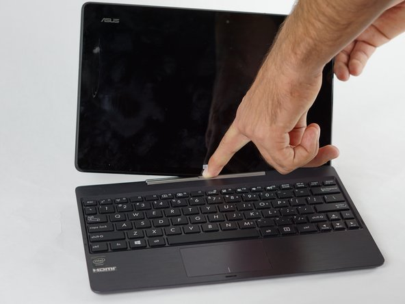 Detach and separate the screen from the keyboard by pressing the silver release button at the base of the tablet.