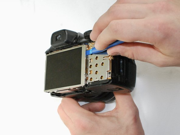 Use a plastic opening tool to separate the LCD screen from the camera.
