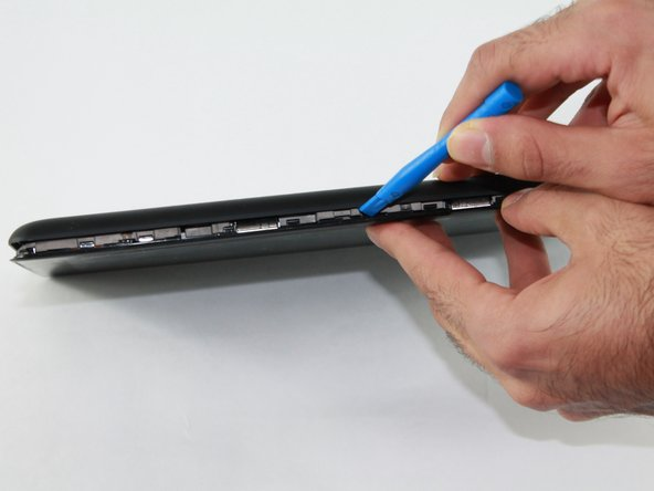 Remove the back panel with the plastic opening tool by sliding the tool around the edge of the panel.