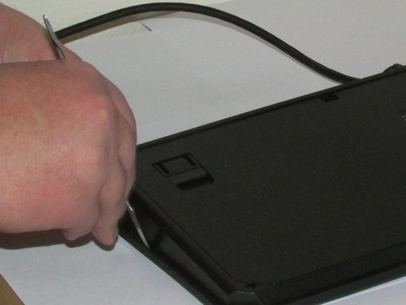 Using a metal spudger, begin prying off the faceplate of the keyboard. There are small tabs along the edge of the keyboard and the faceplate that must be released. There are four tabs along the front of the keyboard and two along each side.