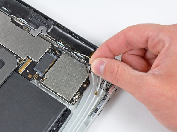 Image 1/2: Pull the communications cable upward to lift its connector up and out of the socket on the logic board.