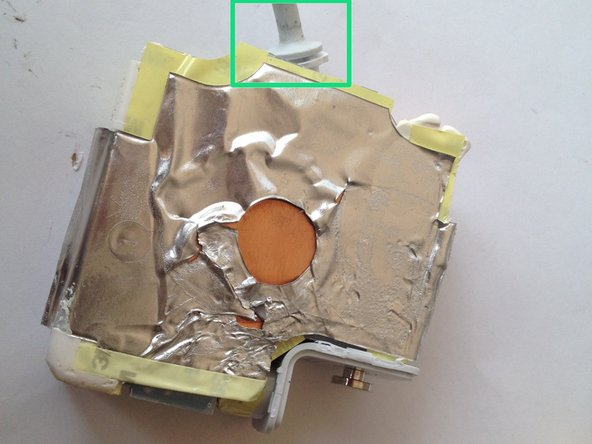 電源アダプタに付いているケーブル上の小さなプラスチック製パーツを掴みます。