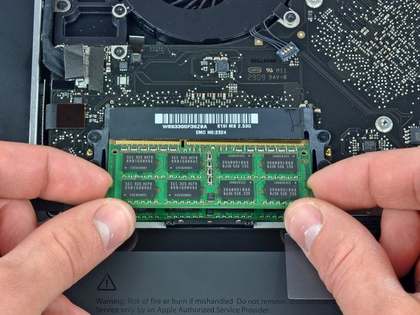 Image 2/2: After the RAM chip has popped up, pull it straight out of its socket.